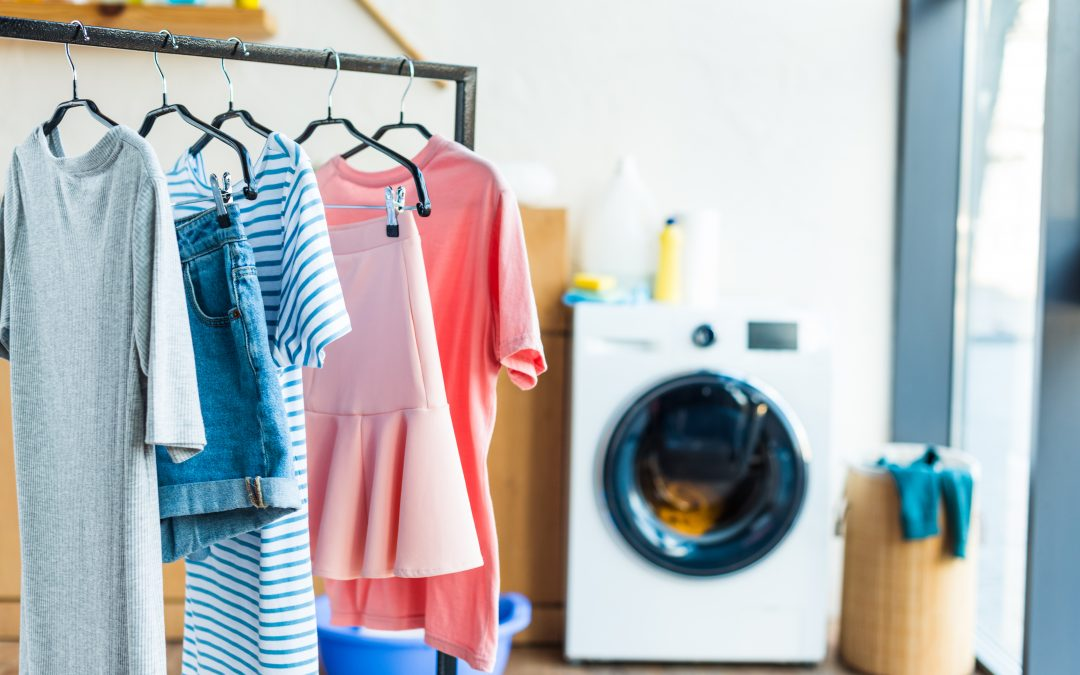 clean clothes hanging up on rack in laundry room